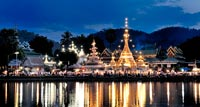 Twin white and gold Shan-style temples on the banks of a shimmering lake