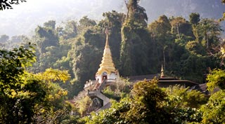 An enchanting, peaceful wat surrounded by mountain forest