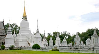 A towering Chedi rises against a backdrop of white, royal mausoleums